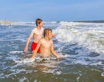Dos muchachos y hermanos adolescentes gozan de las ondas en el océano áspero Foto de archivo