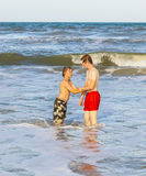 Dos muchachos y hermanos adolescentes gozan de las ondas en el océano áspero Foto de archivo libre de regalías