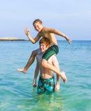 Dos muchachos y hermanos pegan una actitud divertida en el océano Foto de archivo