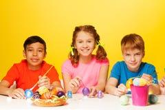 Dos muchachos y la muchacha pintan los huevos de Pascua en la tabla Fotografía de archivo libre de regalías