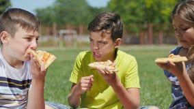 Dos muchachos y muchacha que cenan con la pizza almacen de video
