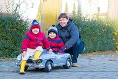 Dos muchachos y padre de los niños que juegan con el coche, al aire libre imágenes de archivo libres de regalías