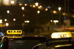Dos muestras del taxi en la noche foto de archivo