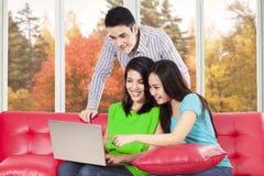 Dos mujer y muchacho que usa el ordenador portátil Imagen de archivo