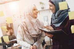 Dos mujeres árabes que trabajan en oficina Los compañeros de trabajo están tomando notas sobre el tablero de cristal foto de archivo
