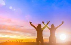 Dos mujeres acertadas felices que aumentan los brazos hacia paisaje hermoso La gente alcanza meta de la blanco de la vida Las muj fotos de archivo libres de regalías