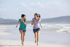Dos mujeres activas que corren y que disfrutan de vida en la playa Fotografía de archivo