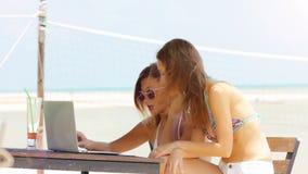 Dos mujeres adultas jovenes que trabajan en el ordenador portátil junto almacen de metraje de vídeo