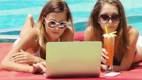 Dos mujeres adultas jovenes que trabajan en el ordenador portátil junto almacen de video
