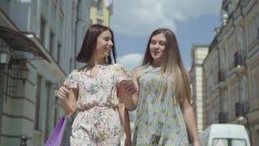 Dos mujeres alegres con los bolsos de compras que caminan a través de la calle de la ciudad Chicas jóvenes que llevan el goce ele metrajes