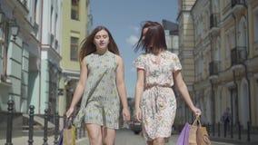 Dos mujeres alegres con los bolsos de compras que caminan a través de la calle de la ciudad Chicas jóvenes que llevan el goce ele almacen de metraje de vídeo