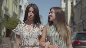Dos mujeres alegres con los bolsos de compras que caminan a través de la calle de la ciudad Chicas jóvenes que llevan el goce ele almacen de video