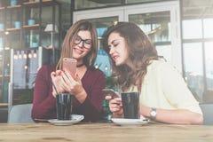 Dos mujeres alegres jovenes se sientan en la tabla en café y utilizan smartphone imágenes de archivo libres de regalías