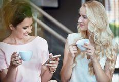Dos mujeres alegres que beben el café y que miran el smartphone Fotos de archivo libres de regalías
