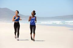 Dos mujeres aptas de los jóvenes que corren en la playa Fotos de archivo
