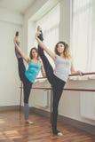 Dos mujeres aptas están haciendo ejercicio del ballet imagen de archivo