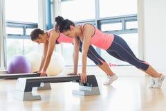 Dos mujeres aptas que realizan aeróbicos del paso ejercitan en gimnasio Fotos de archivo libres de regalías