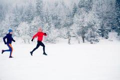 Dos mujeres arrastran el funcionamiento en nieve en montañas del invierno imágenes de archivo libres de regalías