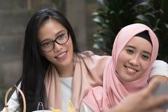 Dos mujeres asiáticas hermosas que miran la cámara mientras que abraza cada uno imagenes de archivo