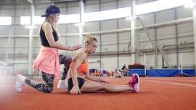 Dos mujeres atléticas jovenes que hacen ejercicios del deporte Hacer estirar almacen de video