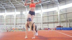 Dos mujeres atléticas jovenes que hacen ejercicios del deporte juntos Salto sobre la parte posterior almacen de video