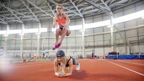 Dos mujeres atléticas jovenes que hacen ejercicios del deporte Salto sobre la parte posterior metrajes