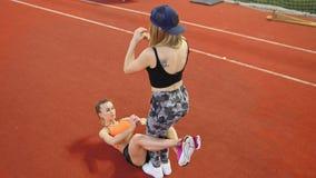 Dos mujeres atléticas jovenes que hacen ejercicios del deporte Una mujer que bombea su ABS almacen de video