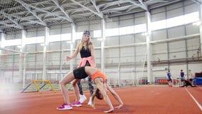Dos mujeres atléticas que hacen ejercicios gimnásticos del deporte Una mujer que dobla encima almacen de video
