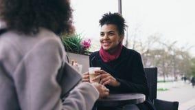 Dos mujeres atractivas de la raza mixta que hablan y que beben el café en café de la calle Los amigos se divierten después de ven fotos de archivo