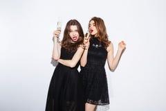Dos mujeres atractivas en champán de consumición del vestido de la noche Foto de archivo libre de regalías