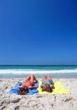 Dos mujeres atractivas jovenes que se enfrían en el sol en día de fiesta o el VAC Imagen de archivo libre de regalías