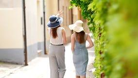 Dos mujeres atractivas que caminan en el callejón y la charla metrajes