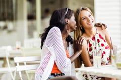 Dos mujeres atractivas que cotillean y que susurran al aire libre en un café Fotografía de archivo libre de regalías