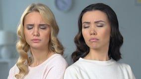 Dos mujeres atractivas que se sientan por separado, mejores amigos que pelean, relaciones metrajes