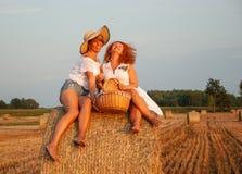 Dos mujeres atractivas se divierten la vid blanca de la bebida de la comida campestre y el tener Imágenes de archivo libres de regalías