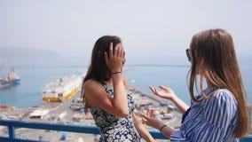 Dos mujeres atractivas se encontraron inesperado en la plataforma de observación en los muelles almacen de video