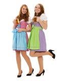 Dos mujeres bávaras con la cerveza en el fondo blanco Fotografía de archivo