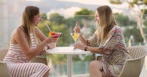 Dos mujeres beben un cóctel en el balcón del hotel en el verano almacen de metraje de vídeo
