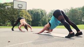 Dos mujeres bien entrenadas hermosas que hacen estirando ejercicios almacen de video