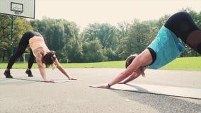 Dos mujeres bien entrenadas hermosas que hacen estirando ejercicios almacen de metraje de vídeo