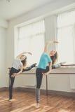 Dos mujeres bonitas aptas están haciendo ejercicio del ballet Foto de archivo
