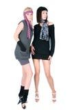 Dos mujeres bonitas de moda que se colocan y que presentan Fotos de archivo libres de regalías