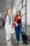 Dos mujeres bonitas están en el terminal con una maleta, una mochila La madre y la hija van el día de fiesta Foto de archivo
