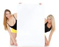 Mujeres jovenes con la tarjeta vacía para el texto. Foto de archivo