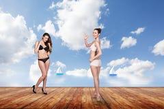 Dos mujeres bonitas jovenes en el embarcadero Imágenes de archivo libres de regalías