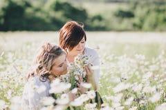 Dos mujeres bonitas jovenes que presentan en una manzanilla colocan Imagen de archivo