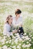 Dos mujeres bonitas jovenes que presentan en una manzanilla colocan Foto de archivo