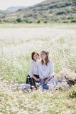 Dos mujeres bonitas jovenes que tienen comida campestre con té en campo de la manzanilla Fotografía de archivo