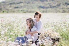 Dos mujeres bonitas jovenes que tienen comida campestre con té en campo de la manzanilla Imágenes de archivo libres de regalías