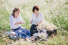 Dos mujeres bonitas jovenes que tienen comida campestre con té en campo de la manzanilla Foto de archivo